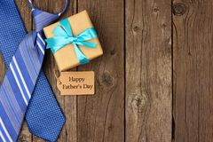 Счастливая граница стороны дня отцов с биркой подарка, подарком и связями на деревенской древесине Стоковые Изображения