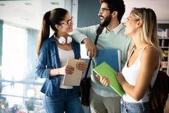 Счастливая группа в составе друзья изучая и говоря совместно в университете стоковые изображения