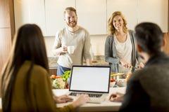 Счастливая группа в составе молодые человеки и женщины варя совместно дома стоковое изображение rf