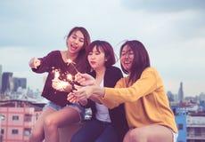 Счастливая группа в составе подруги Азии наслаждается и играется бенгальским огнем на крыше стоковые изображения rf