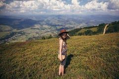 Счастливая девушка битника путешественника в шляпе, идя в солнечные горы Стоковая Фотография RF