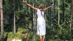 Счастливая девушка в белом платье стоя в лесе с поднятыми руками наслаждаясь летним днем сток-видео