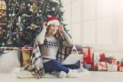 Счастливая девушка в беседовать шляпы santa онлайн на компьтер-книжке Стоковые Изображения RF