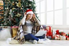 Счастливая девушка в беседовать шляпы santa онлайн на компьтер-книжке Стоковая Фотография