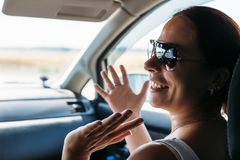 Счастливая девушка в стеклах на сиденье пассажира в автомобиле смеется над стоковые фотографии rf