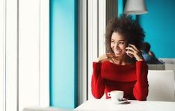 Счастливая девушка говоря на smartphone на кафе Стоковое Изображение