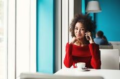 Счастливая девушка говоря на smartphone на кафе Стоковое Изображение RF