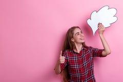 Счастливая девушка держа бумажное изображение мысли или идей надземных смотрящ его и усмехаться Розовая предпосылка стоковые изображения rf