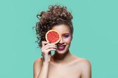 Счастливая девушка держа кусок грейпфрута Стоковые Изображения RF