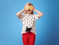 Счастливая девушка держа 2 половины лимона перед стороной на сини Стоковое Изображение RF