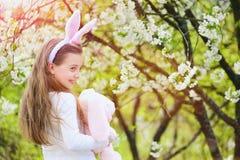 Счастливая девушка держа розового кролика в саде с blossoming деревьями Стоковые Изображения