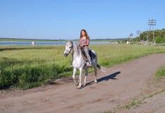 Счастливая девушка ехать верхом, на сельской дороге, против фона озера Стоковая Фотография RF