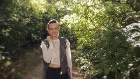Счастливая девушка идя в лес осени и наслаждается своими красотой и солнечным светом которая делают их путь через деревья акции видеоматериалы