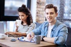 Счастливая девушка и мальчик сидя на таблице и работе Стоковые Изображения