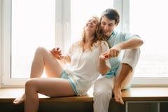 Счастливая девушка и человек обнимая около окна в доме стоковое изображение