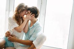 Счастливая девушка и человек целуя около окна в доме стоковое изображение