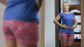 Счастливая девушка любя ее форма тела в зеркале видеоматериал