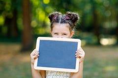 Счастливая девушка маленького ребенка держа пустой стол мела в руках Schoolkid на первый день элементарного класса Здоровое преле стоковая фотография