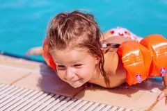 Счастливая девушка малыша имея потеху в бассейне стоковое фото