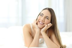 Счастливая девушка мечтая смотрящ сторону на кровати стоковые фотографии rf