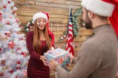 Счастливая девушка получает подарочную коробку рождества от парня indoors стоковое фото rf
