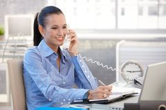 Счастливая девушка работника офиса на телефонном звонке стоковое фото rf