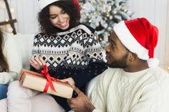 Счастливая девушка развертывая подарок на рождество от ее парня стоковая фотография