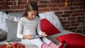 Счастливая девушка ребенка в пижаме Xmas сидя в спальне используя домой украшенную таблетку цифров которую Санта Клаус принес ей, видеоматериал