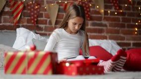 Счастливая девушка ребенка в пижаме Xmas сидя в спальне используя домой украшенную таблетку цифров которую Санта Клаус принес ей, акции видеоматериалы