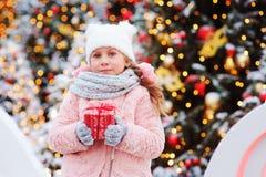 Счастливая девушка ребенка держа подарок рождества внешний на прогулке в снежном городе зимы украшенном на праздники Нового Года стоковое изображение
