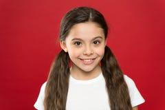 Счастливая девушка ребенка с длинными волосами на красной предпосылке Счастье и утеха взволнованности положительные Уход за детьм стоковая фотография