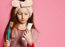 Счастливая девушка ребенка с зубной щеткой чистит зубы и улыбки щеткой стоковые фото