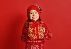 Счастливая девушка ребенка с подарком рождества над красным цветом стоковая фотография rf