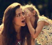 Счастливая девушка ребенк шепча секрету к ее удивительно сотрясенному m Стоковые Изображения RF