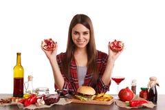 Счастливая девушка сидит на таблице с едой и держит 2 половины гранатового дерева изолировано Стоковые Изображения