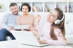 Счастливая девушка сидя на таблице с компьтер-книжкой с ее родителями на bac Стоковое Фото
