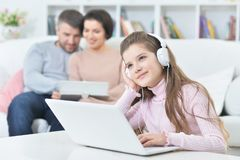Счастливая девушка сидя на таблице с компьтер-книжкой с ее родителями на bac Стоковые Фотографии RF