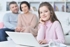 Счастливая девушка сидя на таблице с компьтер-книжкой с ее родителями на bac Стоковое Изображение RF