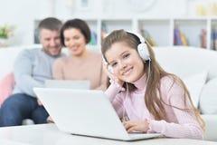 Счастливая девушка сидя на таблице с компьтер-книжкой с ее родителями на bac Стоковые Изображения RF