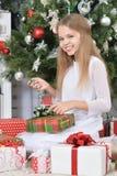 Счастливая девушка сидя с подарками на рождество Стоковые Фото