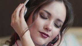 Счастливая девушка слушает музыка в белых наушниках и усмехаться сток-видео