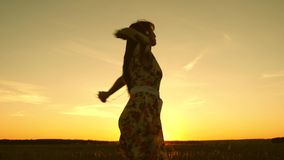 Счастливая девушка слушая музыку и танцуя в лучах красивого захода солнца против неба маленькая девочка в наушниках и видеоматериал