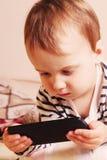 Счастливая девушка смотря мобильный телефон Стоковое Изображение RF