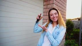 Счастливая девушка стоя близко гараж с ключами автомобиля акции видеоматериалы