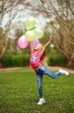 Счастливая девушка с воздушными шарами скача в парк города празднуя свежесть образа жизни лета природы стоковое изображение