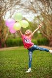 Счастливая девушка с воздушными шарами скача в парк города празднуя свежесть образа жизни лета природы стоковое фото