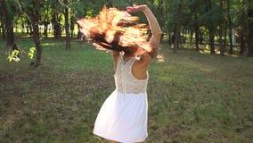 Счастливая девушка с длинными каштановыми волосами в белом коротком платье имея потеху в парке акции видеоматериалы