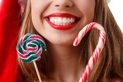 Счастливая девушка с красными губами держит близко стороной 2 конфет рождества и милой улыбки Конец-вверх стоковое изображение