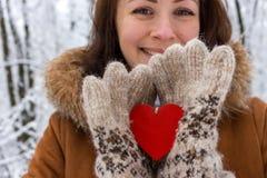 Счастливая девушка с красным деревянным сердцем держа в руках в предпосылке леса зимы несосредоточенной Праздники дня Святого Вал стоковые фото
