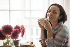 Счастливая девушка с кружкой душистого кофе в руках Хороший завтрак дома в живущей комнате окном Открытый космос для текста стоковые изображения